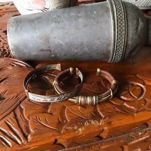 Two cuff bracelets one leather brass one copper